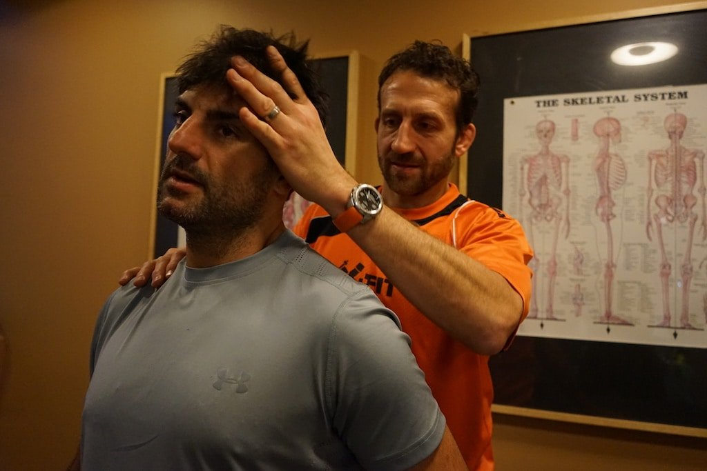 Derek Della Rocca treats a customer for spine alignment in the treatment room with a medical skeleton poster on the wall