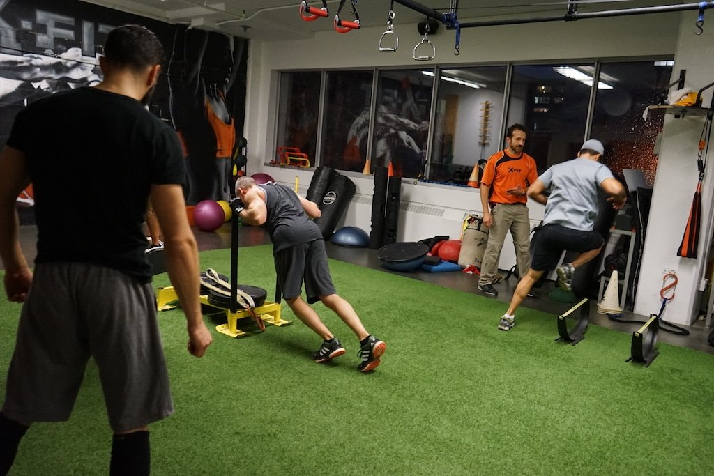 Derek Della Rocca supervising a hurdle exercice while Simon Delquignies spots for a sled push exercice during a group training session