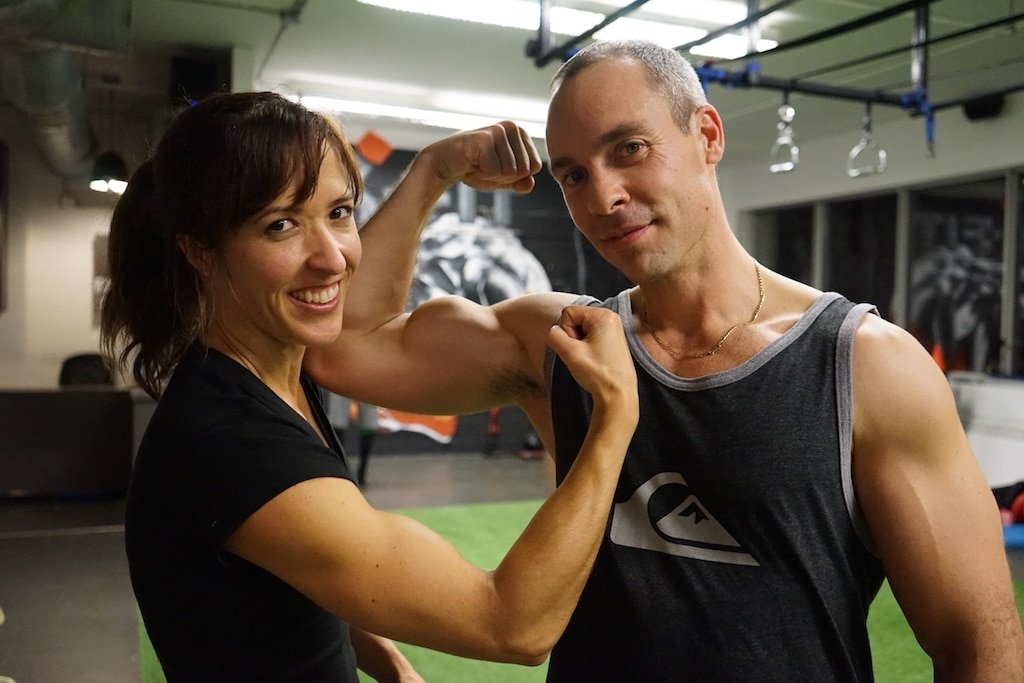 Couple flexing their biceps at the X-Fit gym