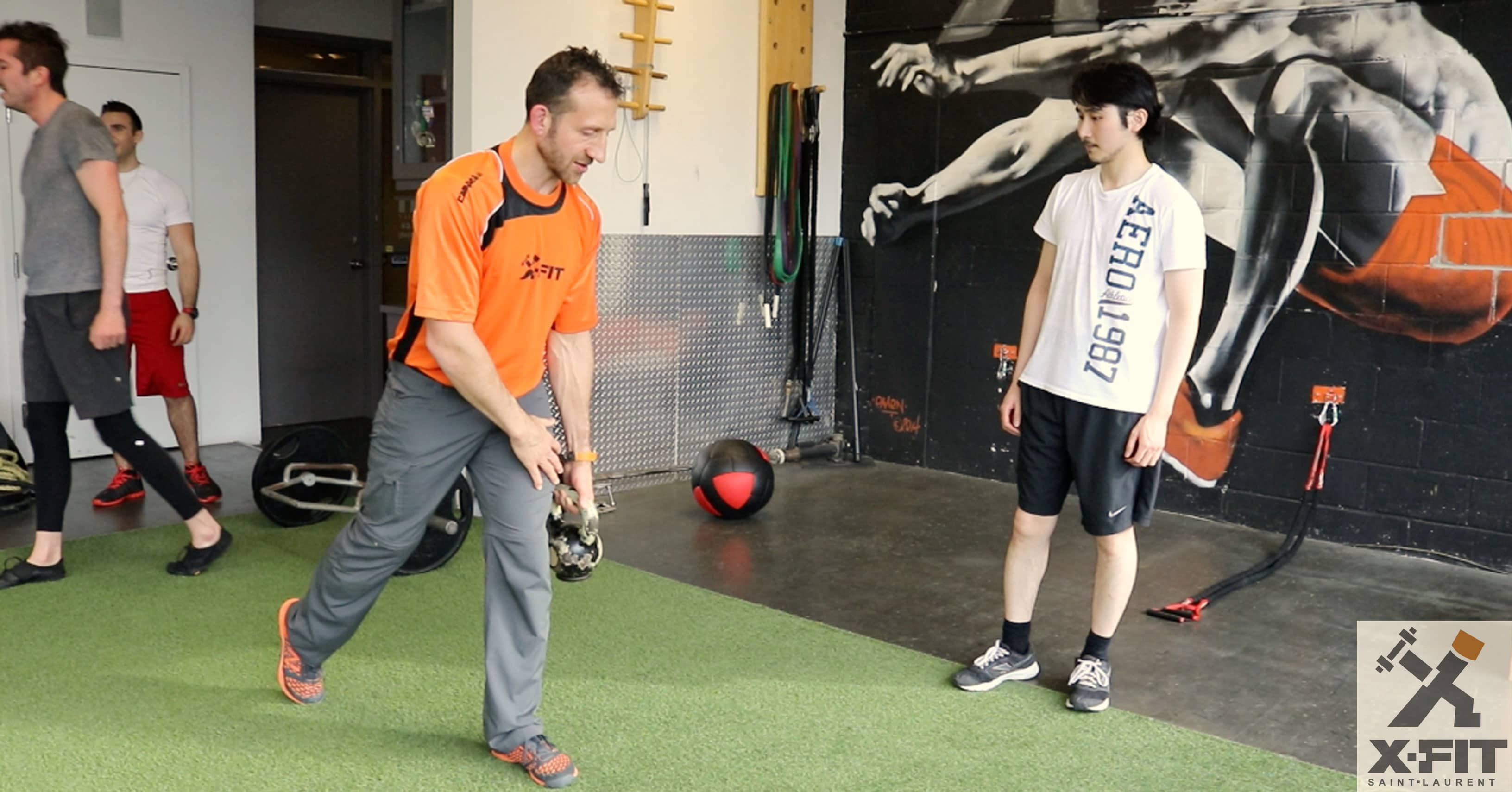 Derek Della Rocca demonstrating kettle bell exercice to a trainee in his gym